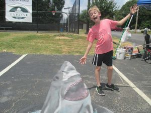A cute child poses with a 3D chalk drawing of a shark