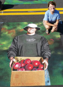A chalk drawing of a man holding a box of apples and the artist Beth Shistle squatting nearby.