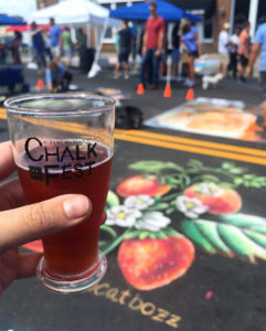 A beer held in front of a strawberry rendered in chalk on the pavement at the Albany, GA Chalk Festival.