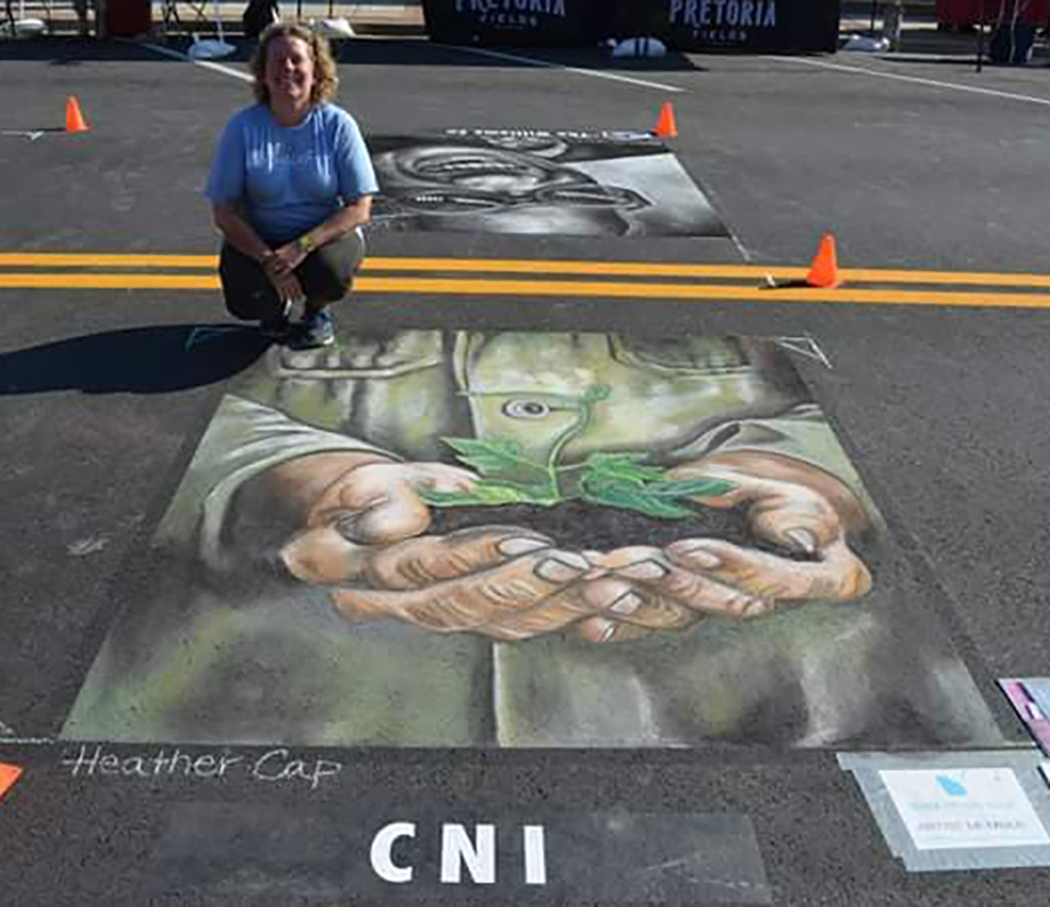 A chalk drawing of hands holding a growing tree and artist Heather Cap.