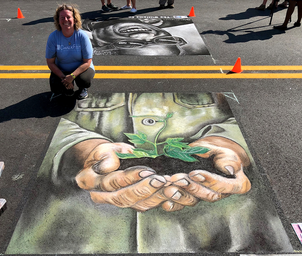 A chalk drawing of hands holding a growing tree and artist Heather Cap at the Albany Street Painting Festival.